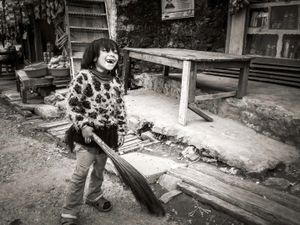 Young girl with a broom, Ranke Bazar, Eastern Nepal