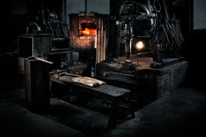 Bladesmith's working space. Oven, power hammer, hammer, anvil and sitting bench are essentials for  the most important process of forging raw steel into the blade.