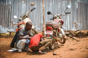 Two men repair a motorcycle at the side of the road. Motorcycles are one of the main forms of transport in Freetown.