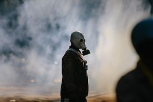 A protester wearing a gas mask walking through a cloud of tear gas fired during a stand-off between anti-Government protesters and police at Government House in Bangkok.