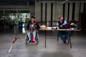 German Gomez, 49, talks with his coach at the Belen Sports Complex, Medellin, April 2016.