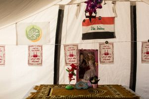 22/01/2015 -- Kirkuk, Iraq -- A family hang up the Iraqi flag and the name of prophet Muhammad inside the tent for the birthday of the prophet Muhammad - Laylan IDP camp, South of Kirkuk.