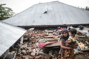 Survivor, Nilawati M. Daud, 30 years old, with her daughter, Maiza, 2 years old, visit her house were destroyed following the earthquake in Pidie Jaya, Aceh province, on December 10, 2016.