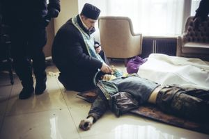 Priest make a funeral service at a field hospital in the hotel Ukraine for a just killed protester by a sniper on Hrushevskoho street. Kiev, Feb. 20, 2014
