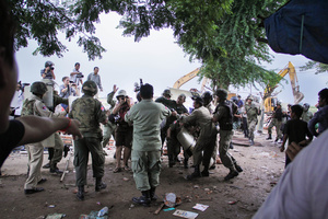 Riot police beat Soung Sorphoan, a former Boeung Kak resident and leader of the opposition Sam Rainsy Party, after he encouraged residents to stop excavators during a forced eviction in Village 22.