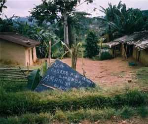 """A roadside sign reads, """"2014, what shall we say again? We ask for lasting peace."""" Yet the Congolese government has been unsuccessful in its attempts to disarm the Kikuni faction of the RM. """"They [FARDC] give the FDLR arms... we can't give arms to FARDC so we store them,"""" explains a soldier. To integrating into the FARDC, Kikuni responds, """"Not into an army of foreigners."""" © Diana Zeyneb Alhindawi"""