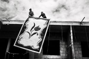 A woman and her sister-in-law clean a rug on the roof of their house in Tirana, Albania © Enri Canaj