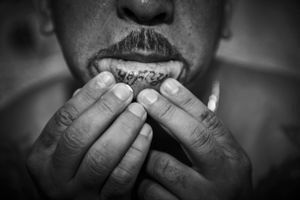 Inmate Olman Orlando aka 'Danger' shows his lip tattoo.