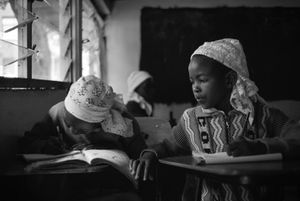 A young Shona girl peers over at another's workbook the two share during a lesson at their school in Nairobi, Kenya, on November 2, 2017.