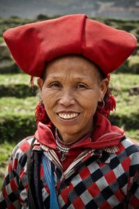 Lady from the Red Dao minority dressed in the traditional red turban with tassels which fall behind her ear and a brightly embroidered shirt.