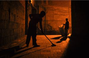 In a quieter alley in Sanaa's old city, two young boys sweep up dust and refuse that have accumulated over the course of the day.
