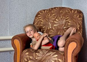 Youngest daughter of eight waiting for lunch. Petrovka, Omsk Oblast, Russia, 2014