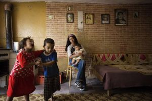 """© Julie Denesha (United States) """"Outcasts of Slovakia"""": Simonka Mirgova and Patko Polhous sing and dance as Sonja Polhousova cares for her nephew Adrian Pista in the home she shares with her parents and siblings. Honorable Mention, LensCulture Exposure Awards 2009"""