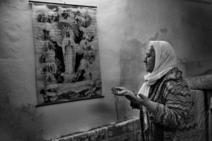 25..3.2015 Kirkuk,Iraq. Najiba is seen while praying to a Christian effigy.
