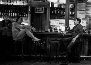 Nude man at a bar