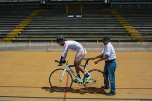 Edwin Matiz, 23, gets ready to start the counter clock training, while his coach Tulio Comcel holds the bicycle on Salitre Sports Complex, Bogotá, June 2016.