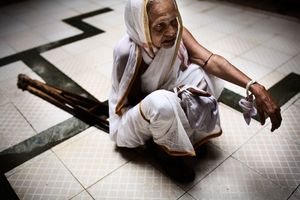 Vrindavan, India, 2009 - A physically challenged widow sits on her sticks during a religious ritual. © Massimiliano Clausi/POSSE Photographers