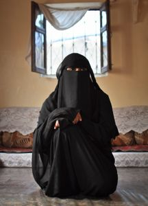 Nadeen sits in her brother's living room, in the home where she lives with her brothers and their families.