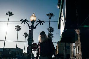 An old, bearded man walks down the street, surrounded by palm trees. Ocean Beach, San Diego.