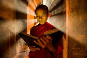 Myanmar monk praying while sunrays engolf his back