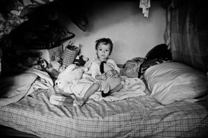 Rebecca (one-year-old) sits on the bed that she and her mother Sandra share in the Alberge in Ixtapec.
