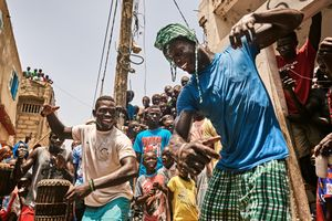 People of the village of Ngor in Dakar gather in front of the house of the family of Kherou Ngor to see the young wrestler performing the wrestler´s dance before the goes to a fight at the Iba mar drop stadium on July 22 2016.
