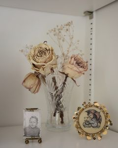 A small photo of Gramps when he was a child, next to dried roses and a Hummel print.