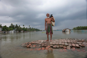 A flood affected man stands on a highland, waits for a boat.