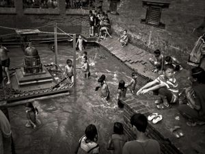 Children swim in a temporary pool during a religious festival.