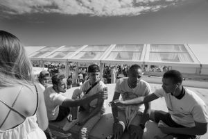 Scoring an invitation to one of the many parties in Cannes during the festival is almost impossible without a direct connection to the film industry.  These  young men are watching from the promenade. 2014  © Alison McCauley