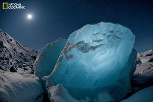 Destined to melt, an 800-pound chunk of ice glowed in the moonlight. It washed up in a lagoon created by a receding glacier, part of a worldwide shrinkage of glacial ice. From the October 125th anniversary issue of National Geographic magazine © James Balog/National Geographic