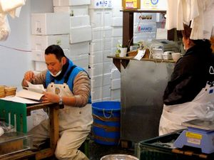 fish trader checking deliveries in his small booth