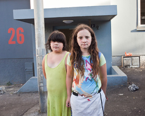 Maddelena, 11 years old, and her sister Ilona, 12 years old, in front of the building (Unit 26) where they live with their parents Thierry and Françoise, and Maddelena'uncle Etienne. During summer, they often spend their time playing in the street as their parents don't have enough money to pay them sport or artistic activities.