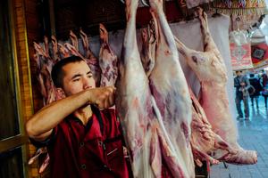 A Uighur man pierced mutton meat as he preparing for a lamb skewers at the restaurant in old Kashgar, Xinjiang Uighur Autonomous Region, China.