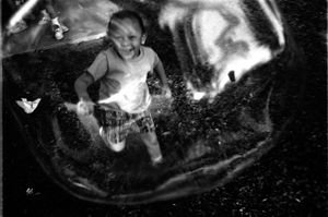 Austin Juarez (4) seen through a soap bubble .  Ethnicity: African • Mexican  ©2014, Stephen Shames