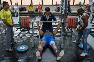 Fabio Torres, 39, lifts 240kgs under the supervision of his coach Henri Oviedo during a training session in the High Performance Center, Bogotá, June 2016.