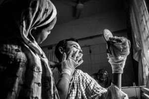 Rehana putting medicine to his husband's burnt face who is a victim of political violence, he is a vegetable vendor and the only earner of their family© Anik Rahman