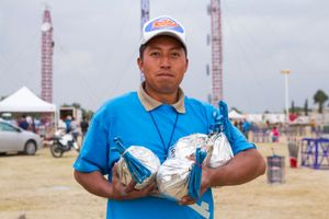 Pyrotechnician holding 'bombs' that explode in light and color.