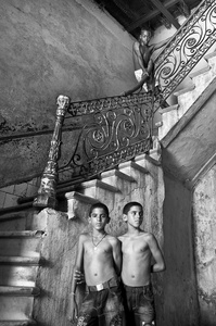 Twins standing in an interior of one of the building on Prado Avenue, across the Capitol in Old Havana.