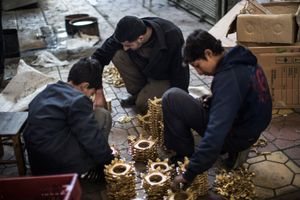 Syrian men sort copper pieces