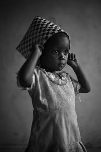 Dixon Ncube's youngest daughter, Baby, stands inside their rented home in Githurai, Nairobi, wearing a Shona basket woven by her as a hat.