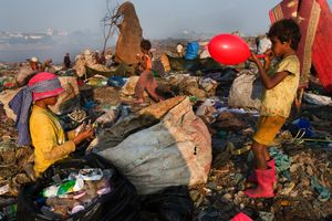 Jakoy, a ten-year old-girl, and recycling worker, blows up a discarded balloon she found on Smokey Mountain. © Nigel Dickinson.