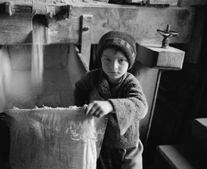 The Millers Boy, Sirbi, 1999. Even though only five, Vasile helps out at his familys mill. First, he adjusts the speed at which corn falls into the millstone to set the cornmeals fineness. Then he holds the bag to catch the ground corn. © Kathleen Laraia McLaughlin.