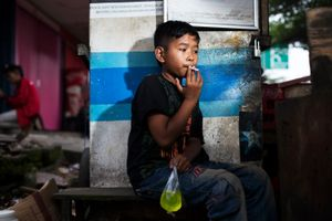 "Eman smokes a cigarette while clutching a bag of juice in Jakarta, Indonesia. He lives on the street and pays a fee to be part of a ""community"" which is similar to a gang. The scar on his forehead is from a fight with a neighboring ""community"" rival. © Michelle Siu"